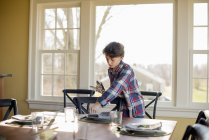 Boy setting the table with cutlery and glasses — Stock Photo