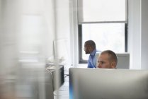 Двое мужчин, работающих в офисе — стоковое фото