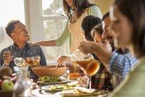 Personas sentadas alrededor de una mesa para una comida - foto de stock