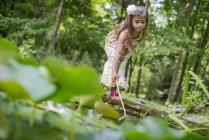 Девушка, играющая у пруда — стоковое фото
