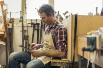 Furniture restorer using digital tablet — Stock Photo