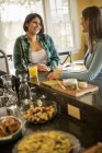 Women seated at a kitchen counter — Stock Photo