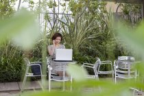Mujer usando un ordenador portátil en un café jardín - foto de stock