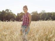 Mulher de pé em um campo de trigo — Fotografia de Stock