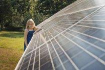 Молодая девушка рядом с солнечной батареей — стоковое фото