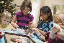 Children decorating organic Christmas cookies — Stock Photo