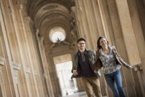 Couple walking down a colonnade — Stock Photo