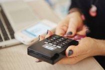 Hände halten ein Kreditkartenlesegerät — Stockfoto
