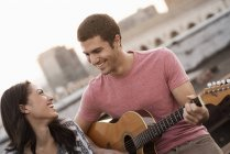 Man playing a guitar to a woman — Stock Photo