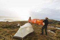 Uomini che tengono e mettendo su una tenda piccola — Foto stock