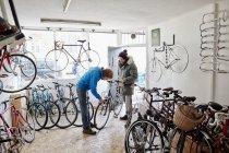 Молодые люди в магазине цикла — стоковое фото