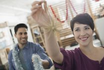 Man and woman holding tinsel and decorations — Stock Photo