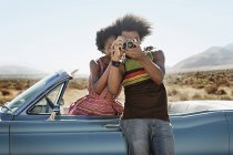 Couple by a pale blue convertible — Stock Photo
