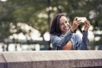 Woman taking selfie with a smart phone — Stock Photo