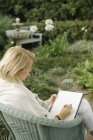 Woman sitting in a garden, writing. — Stock Photo