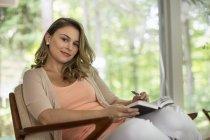 Donna seduta che tiene un giornale aperto — Foto stock
