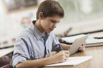 Junge sitzt an einem Schreibtisch — Stockfoto
