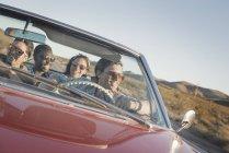 Amis dans une voiture rouge sur un road trip — Photo de stock