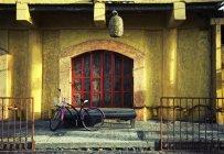 Велосипед припаркован за дверью — стоковое фото
