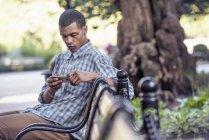 Homme à l'aide de son téléphone intelligent sur banc — Photo de stock