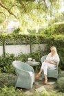 Mulher sentada num jardim — Fotografia de Stock