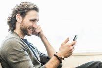Bearded man sitting smiling — Stock Photo