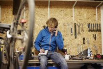 Man with smart phone in a cycle shop — Stock Photo