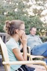 Man and a young girl sitting in a garden. — Stock Photo
