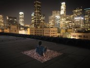 Man sitting on a rug on a rooftop — Stock Photo