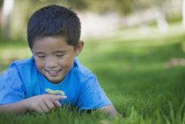 Boy lying on the grass holding a caterpillar — Stock Photo