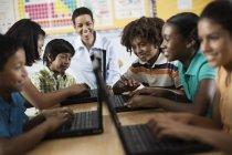 Studenti che utilizzano computer portatili in una lezione . — Foto stock