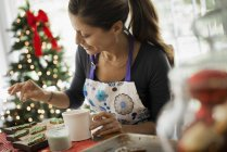 Woman working on homemade Christmas cookies — Stock Photo