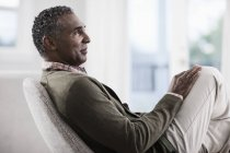 Mature man seated in a chair — Stock Photo