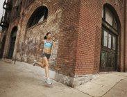 Frau, die entlang einer städtischen Straße — Stockfoto