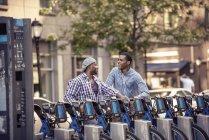 Homens por um rack de bicicletas de aluguer — Fotografia de Stock