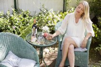 Mulher loira sentada na cadeira de vime — Fotografia de Stock