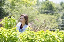 Young woman standing in a garden — Stock Photo