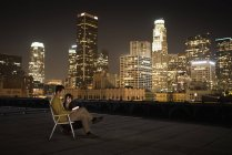Couple on a rooftop overlooking city at night — Stock Photo