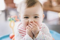 Baby girl with hands covering mouth — Stock Photo