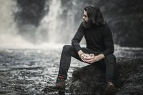 Man sitting by a fast flowing stream — Stock Photo