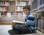 Garçon dans une bibliothèque de lecture d'un livre. — Photo de stock