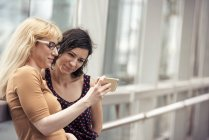 Women looking at a cell phone — Stock Photo