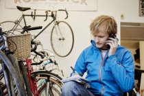 Man making a call in a cycle shop — Stock Photo