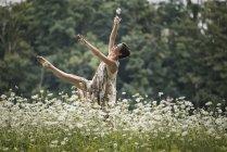 Женщина танцует в поле — стоковое фото