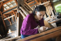 Woman working with reclaimed timber — Stock Photo