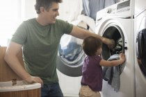 Man and a toddler empyting the laundry — Stock Photo