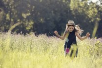 Girl in straw hat in a meadow — Stock Photo