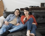 Couple using the remote control for the tv. — Stock Photo