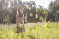 Child walking through grass carrying a book — Stock Photo