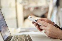 Femme à l'aide d'ordinateur portable et smartphone — Photo de stock
